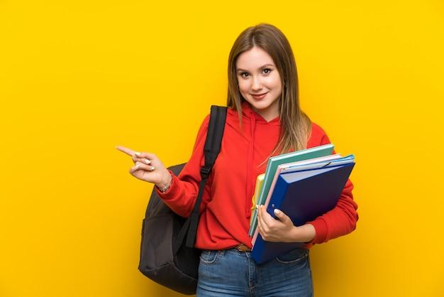 Nastolatek studencka dziewczyna nad kolorem żółtym