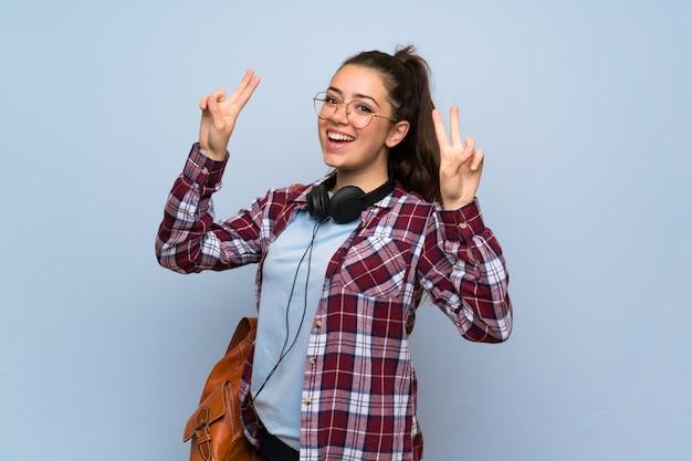 Nastolatek studencka dziewczyna nad odosobnioną błękit ścianą pokazuje zwycięstwo znaka z oba rękami