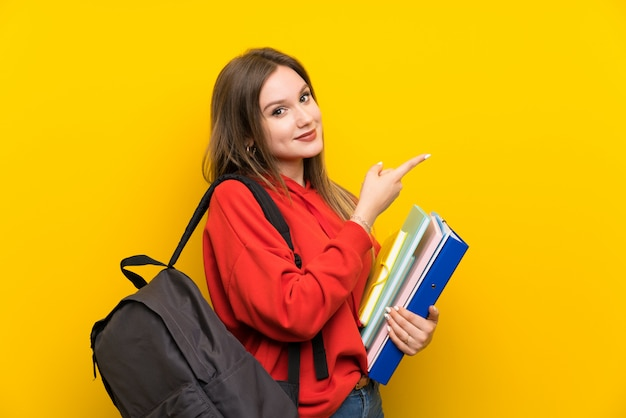 Nastolatek studencka dziewczyna nad żółtym wskazuje palcem strona