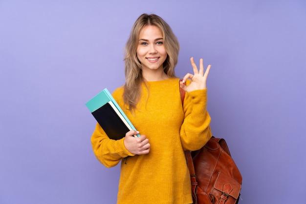 Nastolatek studencka dziewczyna odizolowywająca na purpury ścianie w zen pozie