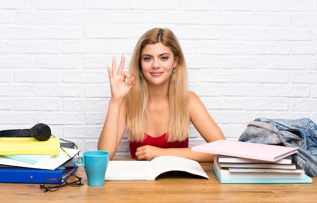 Nastolatek studencka dziewczyna przy indoors pokazuje ok znaka z palcami