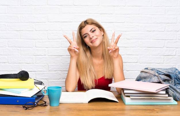 Nastolatek studencka dziewczyna przy indoors pokazuje zwycięstwo znaka z oba rękami