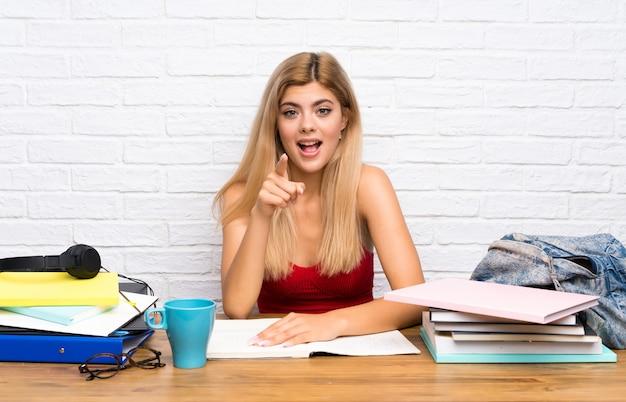 Nastolatek studencka dziewczyna przy indoors zaskakującym i wskazuje przodem
