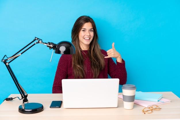 Nastolatek studencka dziewczyna w miejscu pracy nad błękit ścianą