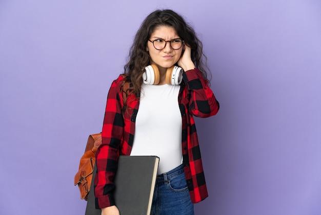 Nastolatek student na białym tle na fioletowym tle sfrustrowani i zakrywający uszy