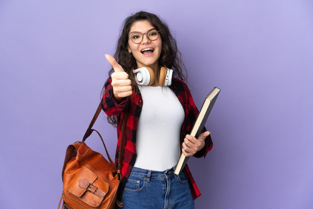 Nastolatek student na białym tle na fioletowym tle z kciukami do góry, ponieważ stało się coś dobrego