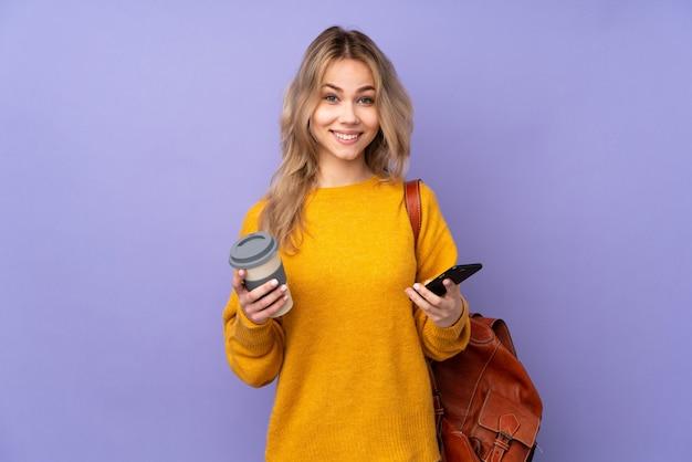 Nastolatek studentka dziewczyna na białym tle na fioletowy trzymając kawę na wynos i telefon komórkowy