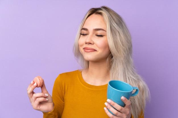 Nastolatek trzyma kolorowych francuskich macarons i filiżankę mleka