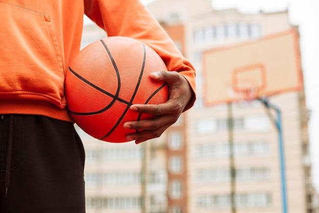 Nastolatek trzyma koszykówkę na zewnątrz