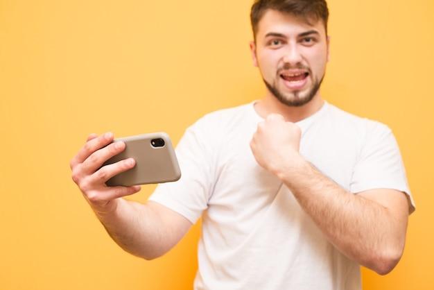 Nastolatek trzyma smartfon w dłoniach i cieszy się ze zwycięstwa