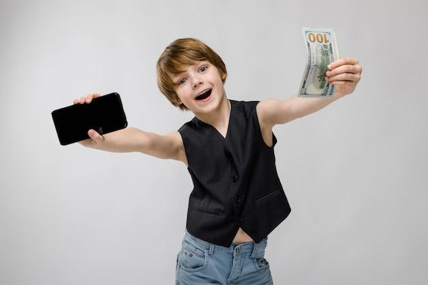 Nastolatek trzyma telefon w jednej ręce, aw drugiej pieniądze. urocza nastolatka o blond włosach i ciemnych oczach. nastolatek jest szczęśliwy