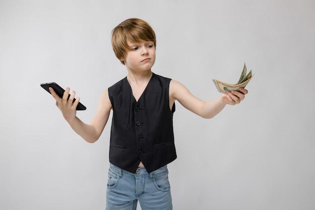 Nastolatek trzyma telefon w jednej ręce, aw drugiej pieniądze. urocza nastolatka o blond włosach i ciemnych oczach.