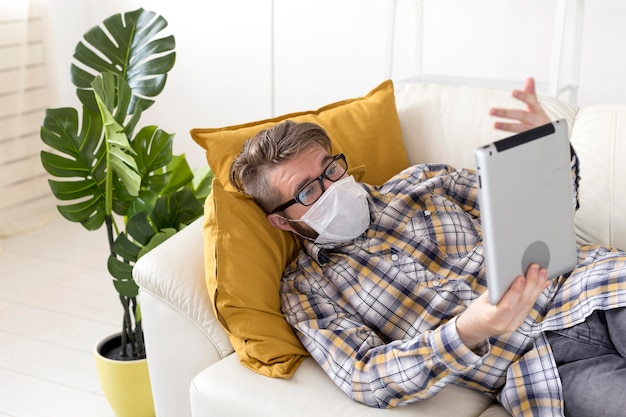 Nastolatek trzymając tabletkę z maską na twarz