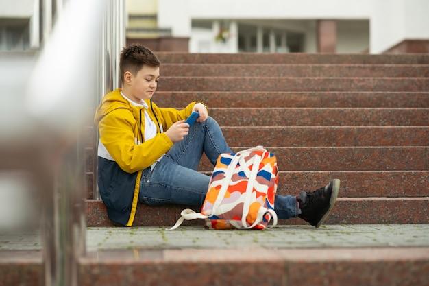 Nastolatek uczeń siedzi na schodach z telefonem w rękach.