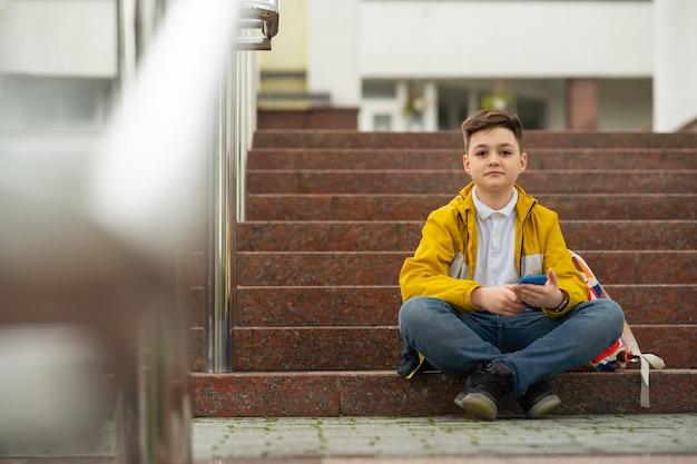 Nastolatek uczeń siedzi na schodach z telefonem