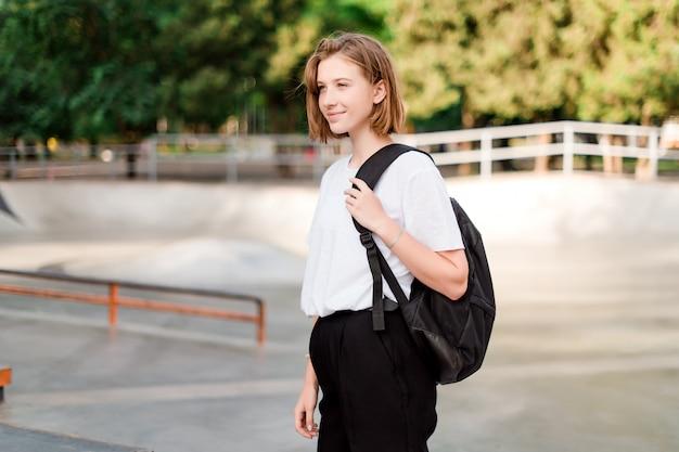 Nastolatek uczeń z szkolnym plecakiem w parku