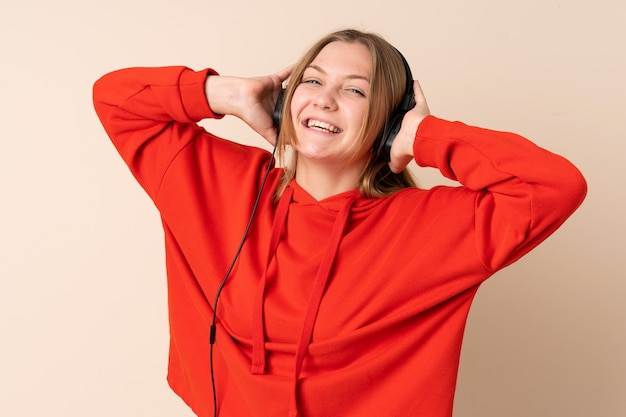 Nastolatek ukraińska dziewczyna odizolowywająca na beżowej słuchającej muzyce