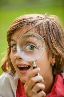 Nastolatek używa lupy do odkrywania natury