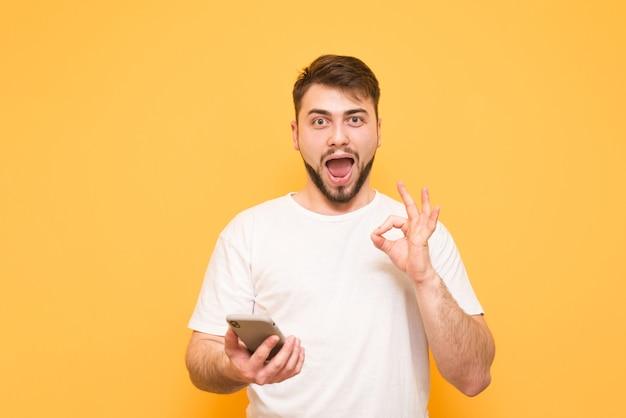 Nastolatek w białej koszulce trzyma w rękach smartfona i na żółtym tle pokazuje ok