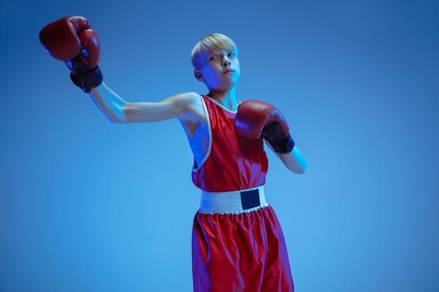 Nastolatek w boksie odzieży sportowej odizolowany na niebieskiej ścianie studia