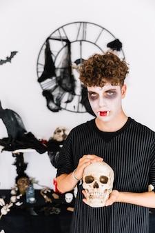 Nastolatek w halloweenowej wampir ponurej mienia czaszce