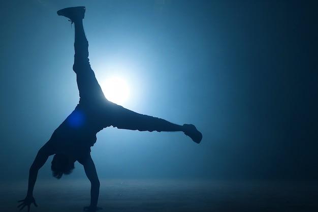 Nastolatek w przypadkowych ubraniach improwizujących w tańcu na świeżym powietrzu. król wykonujący ruchy. umiejętności twórcze.