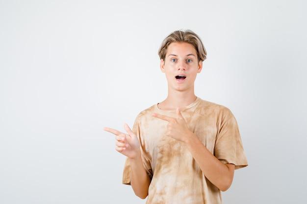 Nastolatek wskazujący w lewo w koszulce i patrzący zdziwiony. przedni widok.