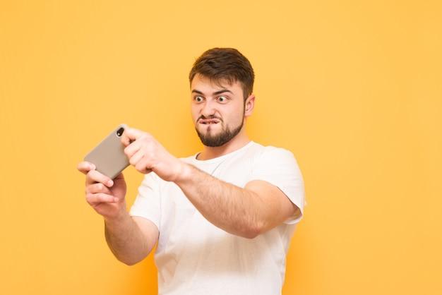 Nastolatek z brodą grając w gry mobilne na smartfonie