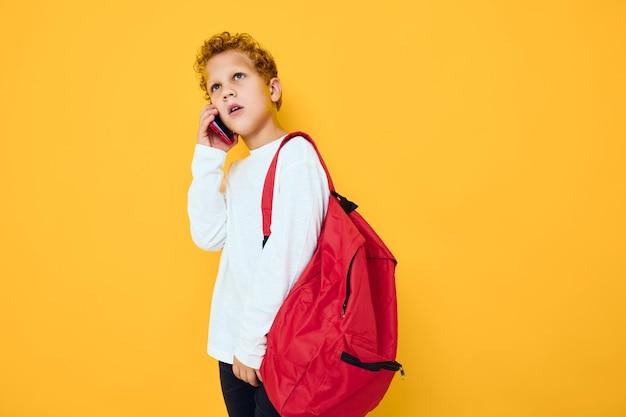 Nastolatek z czerwonym plecakiem dzwoni przez telefon na żółtym tle
