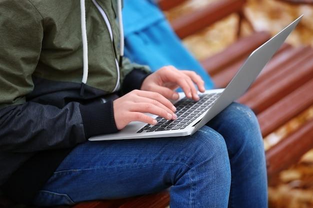 Nastolatek z laptopa siedząc na ławce w jesiennym parku, z bliska