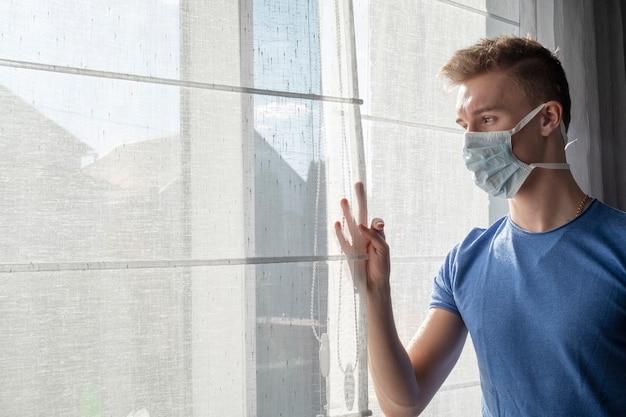 Nastolatek z maską chirurgiczną patrząc przez okno domu. koncepcja kwarantanny. koronawirus
