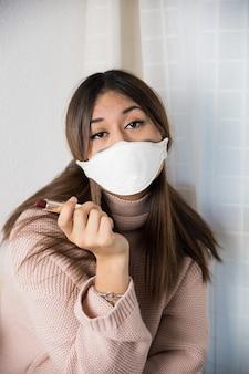 Nastolatek z maską ochronną z wątpliwościami, jak nakładać pomadkę