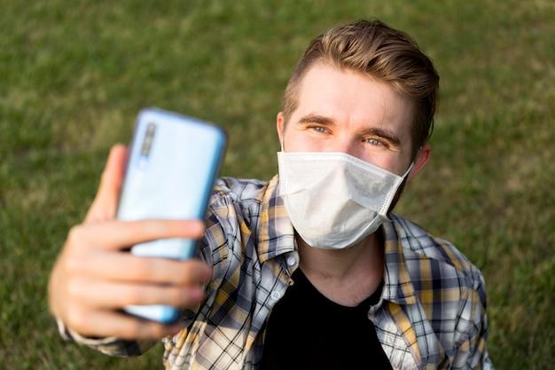 Nastolatek z maską przy selfie