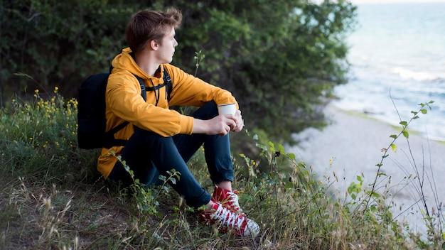 Nastolatek z plecakiem siedzi na ziemi w lesie