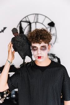 Nastolatek z ponurym wampirem i krukiem na ramieniu