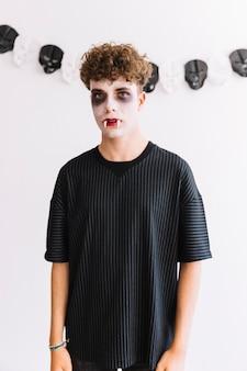 Nastolatek z przerażającym ponurakiem i kłami