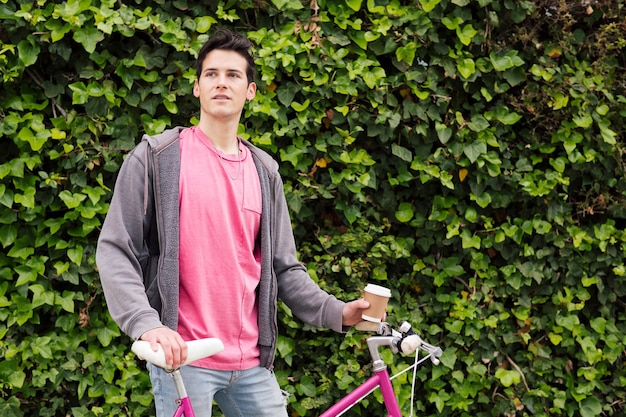 Nastolatek z rocznika roweru na tle roślin