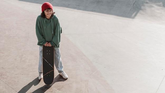 Nastolatek zabawy na deskorolce w skateparku z miejsca na kopię