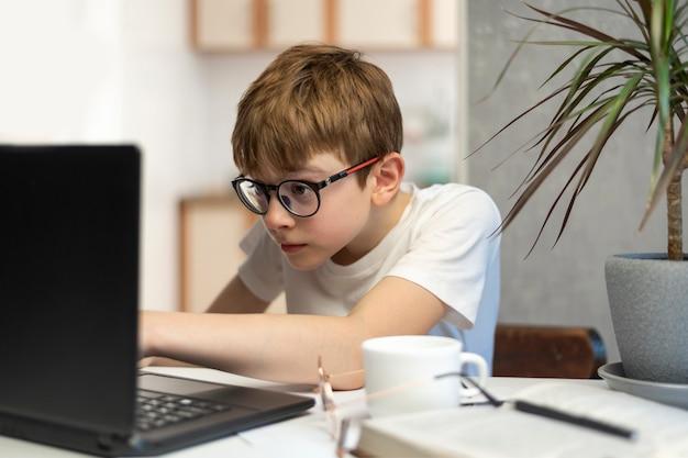 Nastolatek zajmuje się programowaniem. dziecko w okularach wpatruje się w monitor laptopa. nauczanie domowe