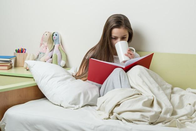 Nastolatka 10 lat w piżamie czyta książkę