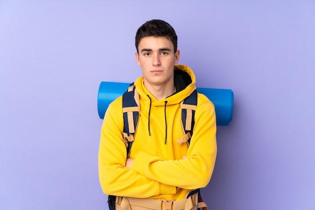 Nastolatka alpinisty caucasian mężczyzna z dużym plecakiem odizolowywającym na purpurowym tle smutnym