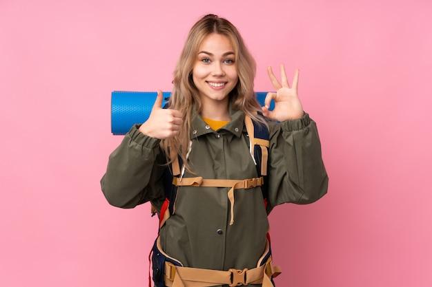Nastolatka alpinisty dziewczyna z dużym plecakiem na menchii ścianie pokazuje ok znaka i kciuka up gestykuluje
