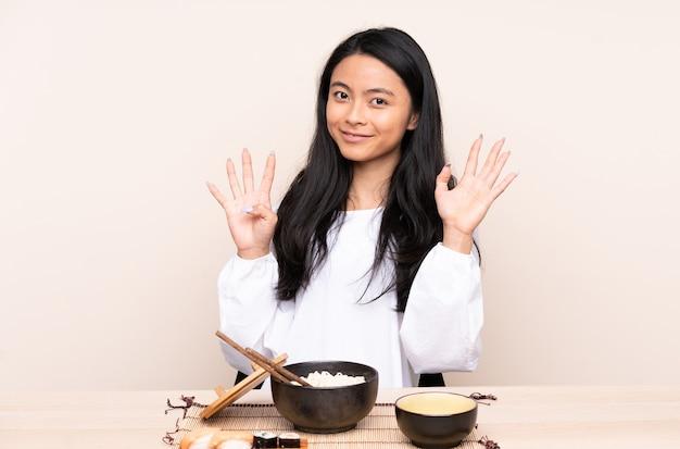 Nastolatka azjatyckie dziewczyny jedzenie azjatyckie jedzenie na białym tle na beż, licząc dziewięć palcami