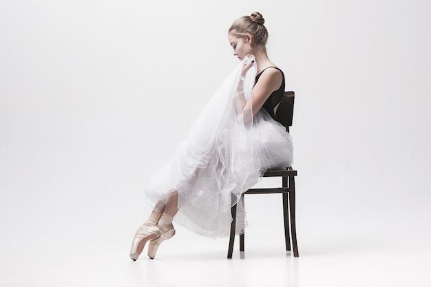 Nastolatka baleriny w białym opakowaniu siedzi na krześle