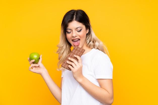 Nastolatka biorąc tabletkę czekolady w jednej ręce i jabłko w drugiej