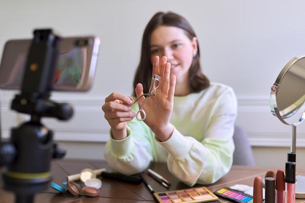 Nastolatka, blogerka piękności, kręci wideo na blogu kanału, pokazując zalotkę. mówienie i pokazywanie makijażu oraz niewidzialny naturalny makijaż. uroda, technologia, komunikacja nastolatków online