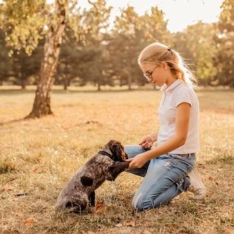 Nastolatka blondynka w dużych okularach, śmiejąc się i bawiąc się małym szczeniakiem