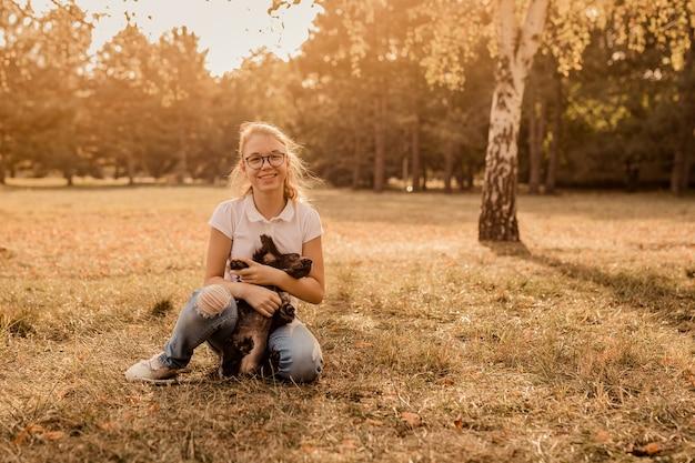 Nastolatka blondynka w dużych okularach, śmiejąc się i bawiąc się z małym szczeniakiem spanielem