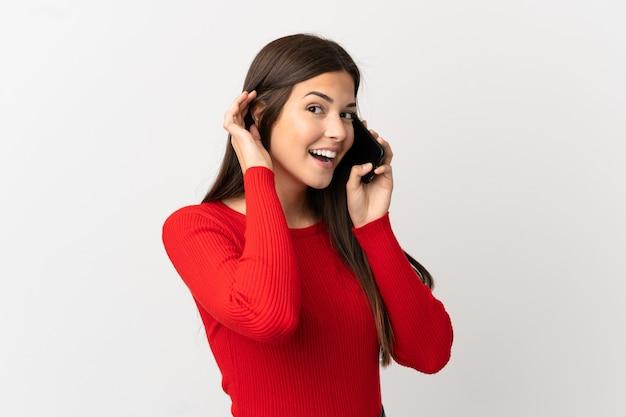 Nastolatka brazylijska dziewczyna przy użyciu telefonu komórkowego na pojedyncze białe tło słuchając czegoś przez umieszczenie ręki na uchu