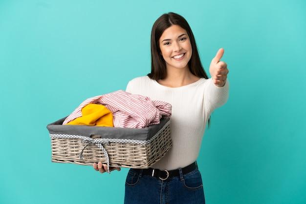 Nastolatka brazylijska dziewczyna trzyma kosz na ubrania na białym tle na niebieskim tle, ściskając ręce, aby zamknąć dobrą ofertę